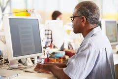 Hombre que trabaja en el escritorio en oficina creativa ocupada fotos de archivo