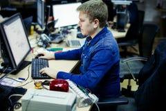 Hombre que trabaja en el frente de la oficina del equipo de escritorio Fotos de archivo libres de regalías