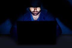 Hombre que trabaja en el ordenador en sitio oscuro Foto de archivo