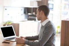 Hombre que trabaja en el ordenador portátil en oficina Imagen de archivo libre de regalías