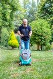 Hombre que trabaja en hierba del corte del jardín con el cortacésped Fotos de archivo