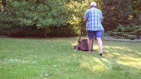 Hombre que trabaja en hierba del corte del jardín con el cortacésped 4K almacen de video
