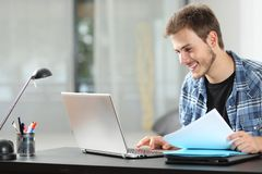 Hombre que trabaja en línea en casa en un ordenador portátil imágenes de archivo libres de regalías