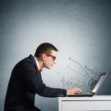 Hombre que trabaja en la computadora portátil Imágenes de archivo libres de regalías