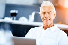 Hombre que trabaja en la computadora portátil en el país Imagen de archivo libre de regalías