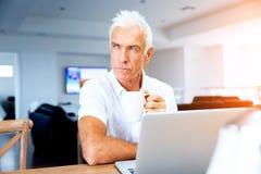 Hombre que trabaja en la computadora portátil en el país Fotos de archivo libres de regalías