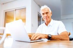 Hombre que trabaja en la computadora portátil en el país Imagenes de archivo