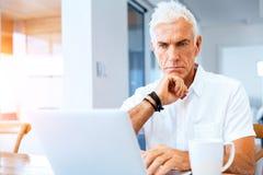 Hombre que trabaja en la computadora portátil en el país Foto de archivo libre de regalías