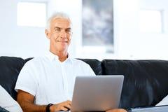 Hombre que trabaja en la computadora portátil en el país Fotografía de archivo libre de regalías