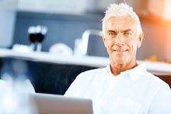 Hombre que trabaja en la computadora portátil en el país Fotos de archivo