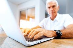 Hombre que trabaja en la computadora portátil en el país Imágenes de archivo libres de regalías