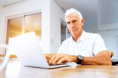 Hombre que trabaja en la computadora portátil en el país Foto de archivo