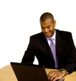 Hombre que trabaja en la computadora portátil en el escritorio Imagenes de archivo