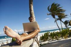 Hombre que trabaja en la computadora portátil remotamente Fotos de archivo