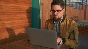 Hombre que trabaja en la PC afuera almacen de video