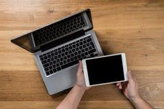 Hombre que trabaja en oficina moderna con el ordenador port?til Visi?n superior imagenes de archivo