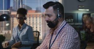 Hombre que trabaja en su escritorio en un centro de atención telefónica