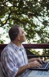 Hombre que trabaja en su ordenador portátil en el balcón foto de archivo