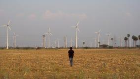 Hombre que trabaja para una compañía del molino de viento en el parque eólico que camina hacia los molinos de viento para la i almacen de metraje de vídeo