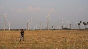 Hombre que trabaja para una compañía del molino de viento en el parque eólico que camina de los molinos de viento después de  almacen de metraje de vídeo