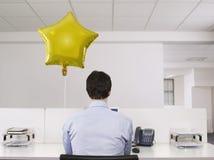 Hombre que trabaja solamente al lado del globo en oficina imagenes de archivo