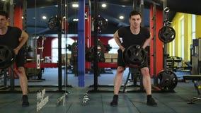 Hombre que trabaja sus brazos en el gimnasio almacen de video