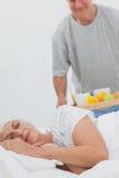 Hombre que trae el desayuno de la esposa el dormir en cama Foto de archivo libre de regalías