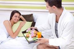 Hombre que trae el desayuno en cama Imágenes de archivo libres de regalías