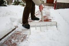 Hombre que traspala nieve en una senda para peatones Fotografía de archivo libre de regalías