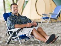 Hombre que usa al jugador mp3 en el sitio para acampar Fotografía de archivo libre de regalías