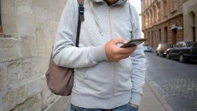 Hombre que usa el app en el teléfono elegante en ciudad vieja metrajes