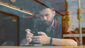 Hombre que usa el app en smartphone en café Tirado a través de ventana metrajes