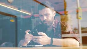 Hombre que usa el app en smartphone en café Tirado a través de ventana almacen de metraje de vídeo