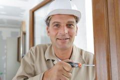 Hombre que usa el destornillador para ajustar la bisagra de puerta fotografía de archivo