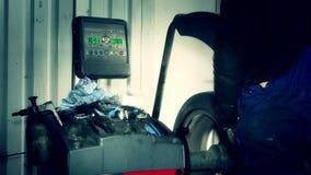 Hombre que usa el equipo automatizado moderno para el equilibrio del neumático de coche almacen de metraje de vídeo