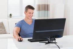 Hombre que usa el equipo de escritorio imagen de archivo
