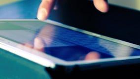 Hombre que usa el finger para la pantalla táctil conmovedora de la PC de la tableta del teclado, estilo azul del color almacen de metraje de vídeo
