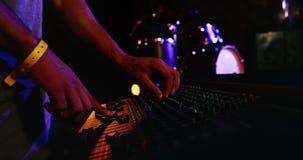 Hombre que usa el mezclador de DJ en el club nocturno 4k almacen de metraje de vídeo