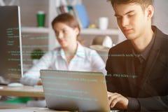 Hombre que usa el ordenador portátil con código del HTML imagenes de archivo