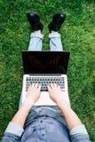 Hombre que usa el ordenador portátil con la pantalla en blanco mientras que se sienta en hierba verde Fotografía de archivo