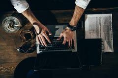 Hombre que usa el ordenador portátil con la pantalla en blanco mientras que se sienta en la tabla con el periódico, el cenicero y Fotografía de archivo libre de regalías