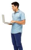 Hombre que usa el ordenador portátil contra el fondo blanco Fotos de archivo