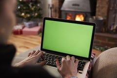 Hombre que usa el ordenador portátil en el sitio adornado para la Navidad imagen de archivo