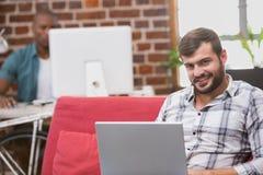 Hombre que usa el ordenador portátil en el sofá en oficina Fotos de archivo