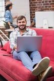 Hombre que usa el ordenador portátil en el sofá en oficina Fotografía de archivo