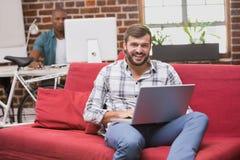 Hombre que usa el ordenador portátil en el sofá en oficina Fotos de archivo libres de regalías