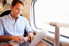 Hombre que usa el ordenador portátil en el tren Fotografía de archivo