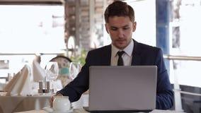 Hombre que usa el ordenador portátil en la hora de comer almacen de metraje de vídeo