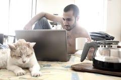 Hombre que usa el ordenador portátil en su cama mientras que bebe el café Imagenes de archivo