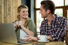 Hombre que usa el ordenador portátil mientras que mira a la mujer en cafetería Imágenes de archivo libres de regalías